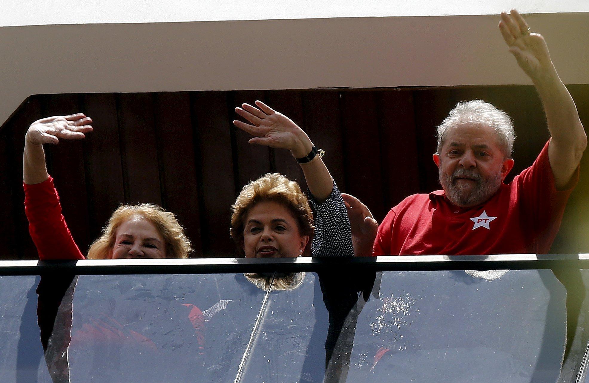 Former Brazilian President Luiz Inacio Lula da Silva (R), his wife Marisa and Brazilian President Dilma Rousseff (C) wave from the window of his home in Sao Bernardo do Camopo, Brazil, March 5, 2016. REUTERS/Paulo Whitaker TPX IMAGES OF THE DAY